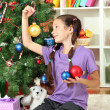 Little girl decorating christmas tree — Stock Photo #16776011