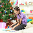 Little girl writing letter to Santa near christmas tree — Stock Photo