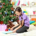 Little girl writing letter to Santa near christmas tree — Stock Photo #16776025