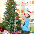 Little girl decorating christmas tree — Stock Photo #16776047
