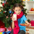 Little girl with pink scarf and glass of milk sitting near christmas tree — Stock Photo #16776059