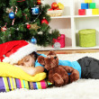 Little girl sleeping near christmas tree — Stock Photo #16776079