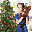 Little girl holding toy near christmas tree — Stock Photo #16776085