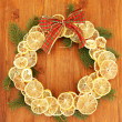 Christmas wreath of dried lemons with fir tree and bow, on wooden background — Stock fotografie