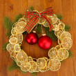Christmas wreath of dried lemons with fir tree and balls, on wooden background - Zdjęcie stockowe