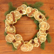 Christmas wreath of dried lemons with fir tree on wooden background — Photo