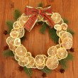 Christmas wreath of dried lemons with fir tree and bow, on wooden background — Foto de Stock