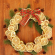 Christmas wreath of dried lemons with fir tree and bow, on wooden background - Zdjęcie stockowe