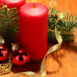 Two candles and christmas decorations, on wooden background — Stock Photo #16776439