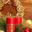 Two candles and christmas decorations, on wooden background - ストック写真