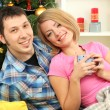 Young happy couple near a Christmas tree at home — Stock Photo #16777451