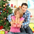 Young happy couple with presents sitting near Christmas tree at home — Stock Photo #16777469