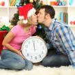 Young happy couple holding clock near Christmas tree at home — Stock Photo #16777477