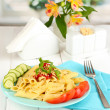Rigatoni pasta dish with tomato sauce on white wooden table in cafe - Foto Stock