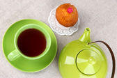 Top view of cup of tea and teapot on tablecloths — Stock Photo