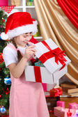 A little girl opens a gift in festively decorated room — Stock Photo