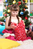 A little girl gets gifts from bag of Santa Claus in festively decorated room — Stock Photo
