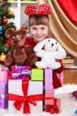 Beautiful little girl in red dress surrounded by gifts and toys in festively decorated room — Stock Photo
