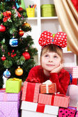Dreaming little girl in red dress surrounded by gifts in festively decorated room — Stock Photo