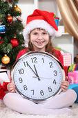 Linda garotinha com relógio na expectativa de ano novo no quarto festivamente decorado — Foto Stock