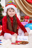 Beautiful little girl with milk and cookies for Santa Claus in festively decorated room — Stok fotoğraf