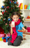Little girl with pink scarf and glass of milk sitting near christmas tree — Foto Stock