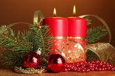 Dos velas y adornos navideños, sobre fondo marrón — Foto de Stock