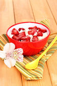 Cottage cheese in red bowl with sliced strawberries on wooden table — Stockfoto