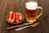 Bira ve ahşap zemin üzerinde ızgara sosis — Stok fotoğraf