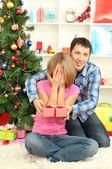 年轻快乐夫妇与坐在圣诞树在家附近的礼物 — 图库照片