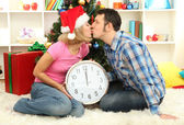 Young happy couple holding clock near Christmas tree at home — Stock Photo