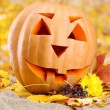 Royalty-Free Stock Photo: Halloween pumpkin and autumn leaves, on yellow background