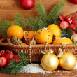 Christmas composition in basket with oranges and fir tree, on wooden background — Photo