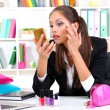 Young business woman looking in the mirror and putting some makeup by office work — Stock Photo #16804019