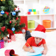 Little boy in Santa hat writes letter to Santa Claus — Stock Photo #16804629