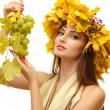 Beautiful young woman with yellow autumn wreath and grapes, isolated on white — Stock Photo #16804731