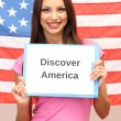 Young woman young woman holding tablet on background of American flag — Stock Photo #16804885