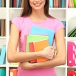 Young attractive female student holding her school books in library — Stock Photo #16804899