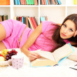 Young female relaxing on floor at home reading book — Stock Photo