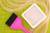 Hair dye in bowl and brush for hair coloring on green bamboo mat, close-up — Stock Photo