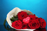 Beautiful bouquet of red roses with valentine on blue background — Stock Photo
