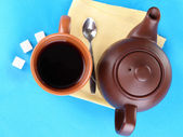 Top view of cup of tea and teapot on blue tablecloths — Stock Photo