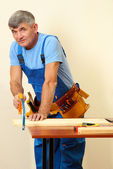 Builder sawing boards on table on wall background — Stock Photo