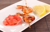 Shrimp skewers on plate with ginger and lemon — Stock Photo