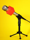 Microphone on stand on yellow background — Stock Photo