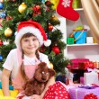 Little girl in Santa hat near the Christmas tree in festively decorated room — Стоковое фото #16839649