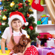 Little girl in Santa hat near the Christmas tree in festively decorated room — Stock Photo