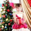 Beautiful little girl in holiday dress with gift in their hands in festively decorated room — Stock Photo #16839651