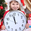 Beautiful little girl with clock in anticipation of New Year in festively decorated room — Zdjęcie stockowe #16839655