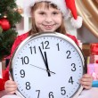Beautiful little girl with clock in anticipation of New Year in festively decorated room — Foto Stock #16839655